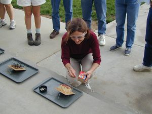 woman outside conducting fire experiment with spectators in background